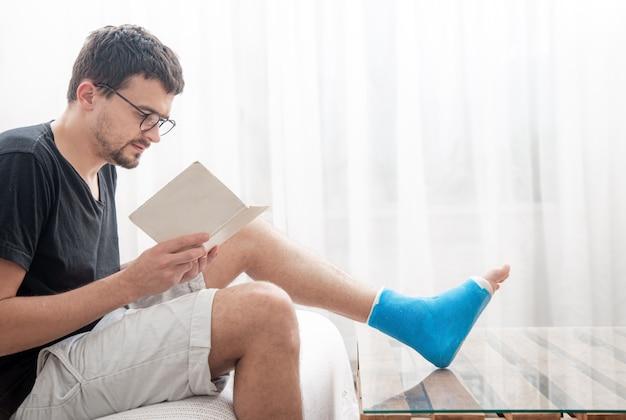 Młody mężczyzna ze złamaną nogą w gipsie czyta książki na jasnej ścianie wnętrza pokoju.
