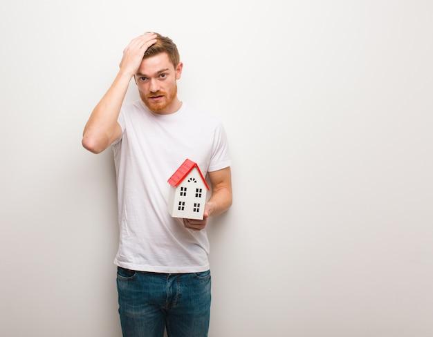 Młody mężczyzna zmartwiony i przytłoczony. trzymanie modelu domu.