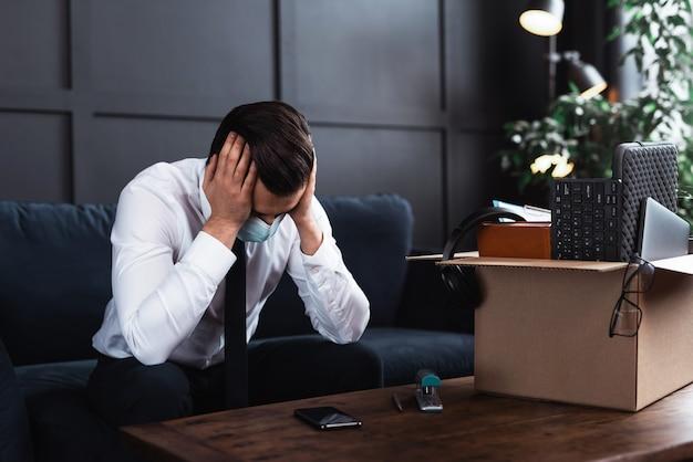 Młody mężczyzna zostaje zwolniony z pracy z powodu pandemii wirusów. biznesmen i karton z jego osobistymi rzeczami z pracy.