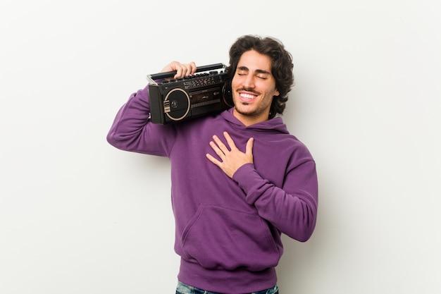 Młody miejski mężczyzna trzymający blaster guetto śmieje się głośno, trzymając rękę na piersi.