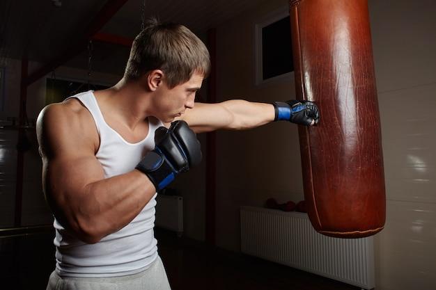Młody mięśni mężczyzna bokser worek treningowy we wnętrzu siłowni