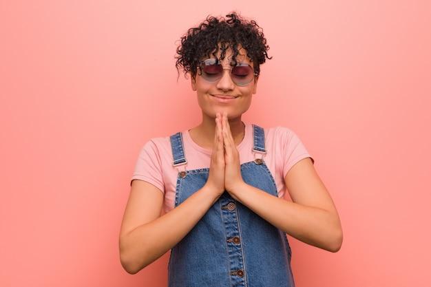 Młody mieszane african american nastolatek kobieta trzymając się za ręce w modlić się w pobliżu usta, czuje się pewnie.