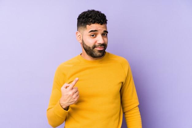 Młody mieszanej rasy arabski mężczyzna na białym tle wskazując palcem na ciebie, jakby zapraszając podejść bliżej.