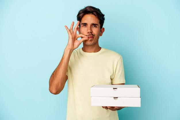 Młody mieszanej rasy człowiek posiadający pizze na białym tle na niebieskim tle z palcami na ustach zachowując tajemnicę.