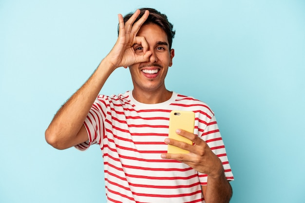 Młody mieszanej rasy mężczyzna posiadający telefon komórkowy na białym tle na niebieskim tle podekscytowany, trzymając ok gest na oko.