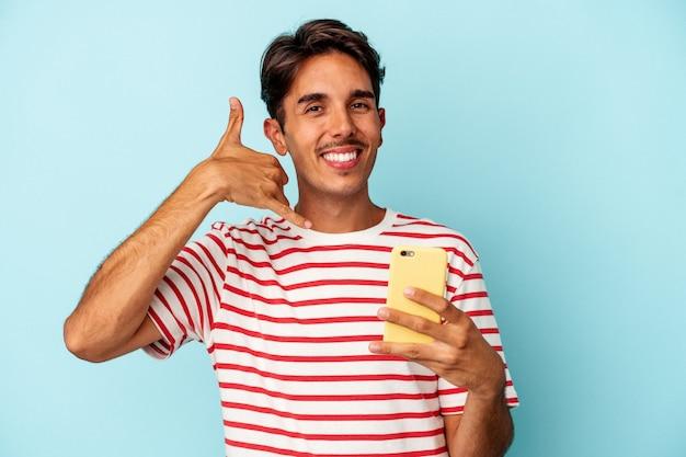 Młody mieszanej rasy mężczyzna posiadający telefon komórkowy na białym tle na niebieskim tle pokazujący gest połączenia z telefonem komórkowym palcami.