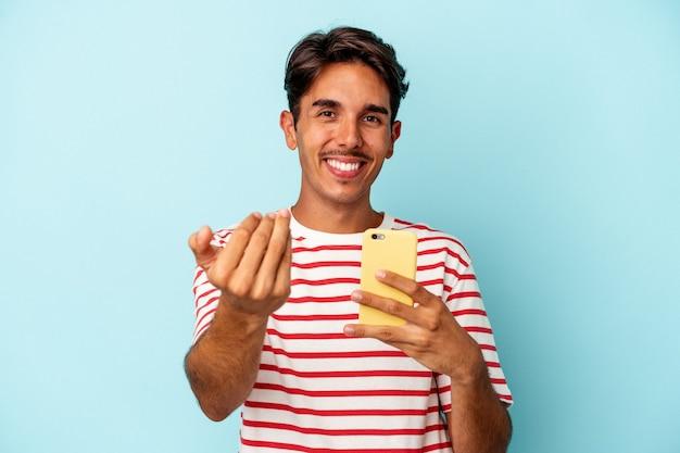 Młody mieszanej rasy mężczyzna posiadający telefon komórkowy na białym tle na niebieskim tle wskazując palcem na ciebie, jakby zapraszając się bliżej.