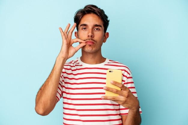 Młody mieszanej rasy mężczyzna posiadający telefon komórkowy na białym tle na niebieskim tle z palcami na ustach zachowując tajemnicę.