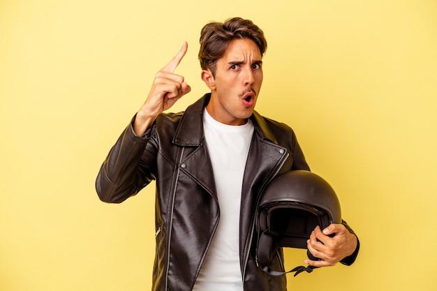 Młody mieszanej rasy mężczyzna trzyma kask na białym tle na żółtym tle o pomysł, koncepcja inspiracji.