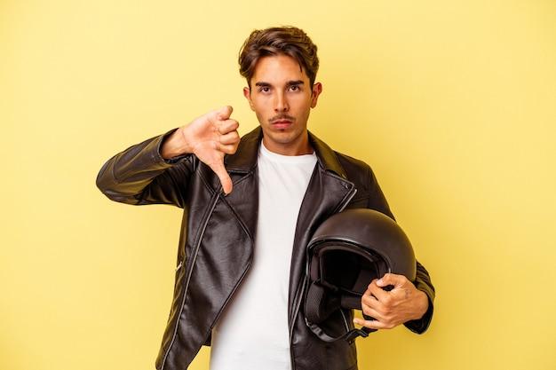 Młody mieszanej rasy mężczyzna trzyma kask na białym tle na żółtym tle pokazując gest niechęci, kciuk w dół. koncepcja niezgody.