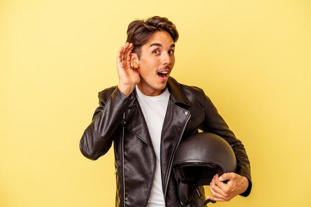 Młody mieszanej rasy mężczyzna trzyma kask na białym tle na żółtym tle próbuje słuchać plotek.
