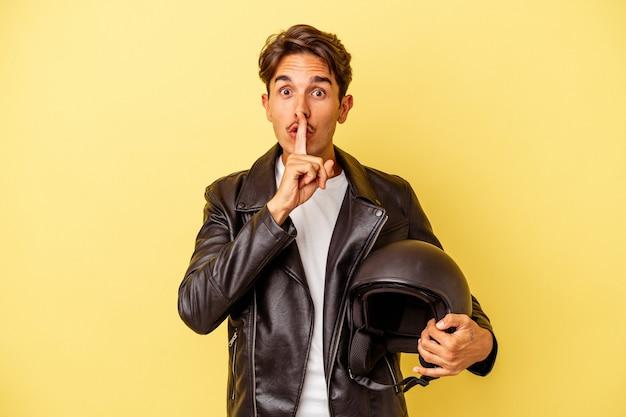 Młody mieszanej rasy mężczyzna trzyma kask na białym tle na żółtym tle zachowując tajemnicę lub prosząc o ciszę.