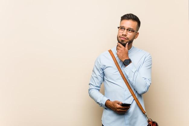Młody mieszany biegowy azjatykci biznesowy mężczyzna trzyma telefon patrzeje z ukosa z wątpliwym i sceptycznym wyrażeniem.