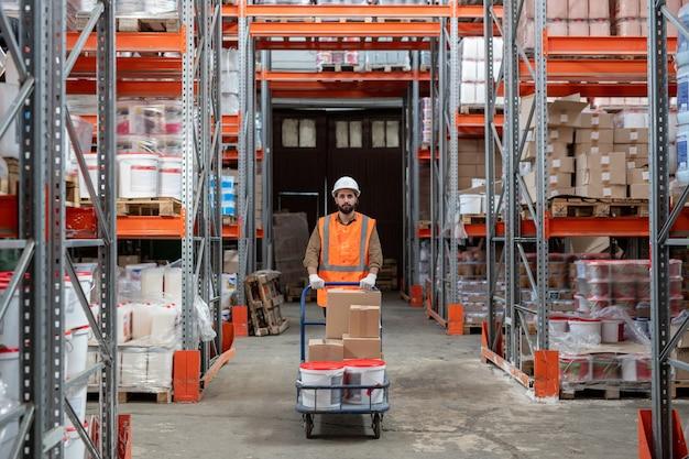 Młody mieszany pracownik rasy w kasku i pomarańczowej kamizelce pcha wózek magazynowy podczas sortowania pudeł w magazynie