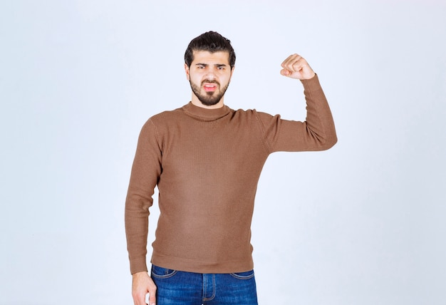 Młody miły model człowieka stojącego i pokazujący jego biceps na białej ścianie. zdjęcie wysokiej jakości