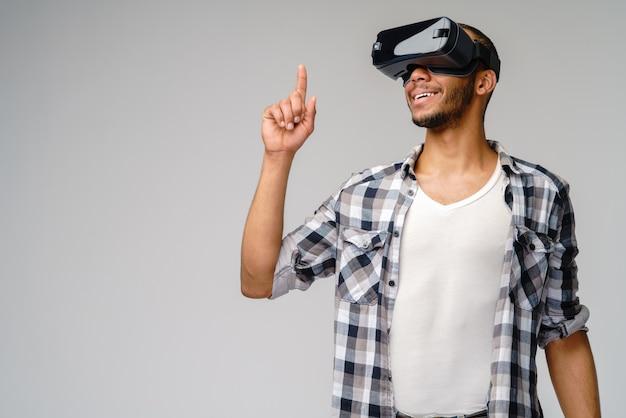 Młody młody człowiek ubrany w zestaw słuchawkowy wirtualnej rzeczywistości vr na jasnoszarej ścianie