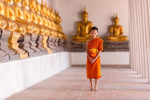 Młody mnich-nowicjusz idący do medytacji w świątyni wat phutthai sawan, ayutthaya, tajlandia