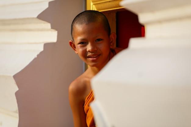 Młody mnich nowicjusz uśmiech w klasztorze duża świątynia okna