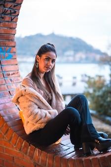 Młody model brunetka siedzi w zimie z miastem w tyle