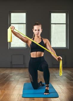 Młody model fitness kobieta lekkoatletka w odzieży sportowej robi rozciągający trening z gumowym ekspanderem. kulturystyka obraz koncepcja zdrowego stylu życia, kopia przestrzeń.