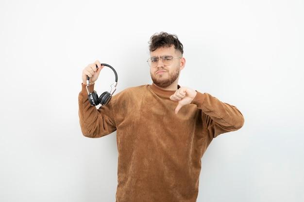 Młody model mężczyzna trzyma czarne słuchawki i daje kciuk w dół.