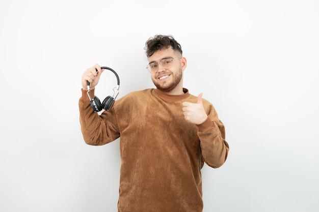 Młody model mężczyzna trzyma czarne słuchawki i daje kciuki do góry.