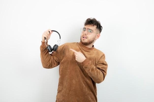 Młody model mężczyzna trzyma czarne słuchawki.