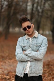 Młody model mężczyzna w stylowej dżinsowej niebieskiej kurtce spacery po parku
