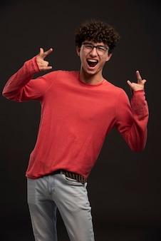 Młody model w czerwonej koszuli pozowanie na castingach z krzykiem.
