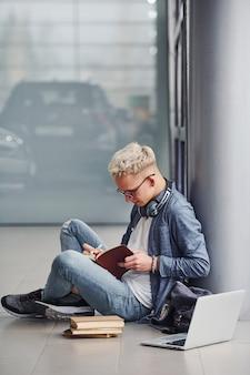 Młody modnisia facet siedzi indoors z laptopem i książkami