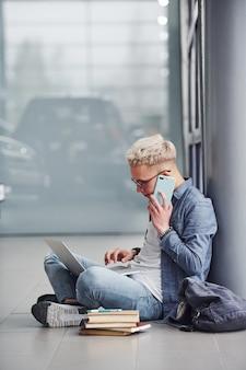 Młody modnisia facet siedzi w domu z laptopem i książkami z telefonem