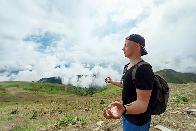 Młody modnisia mężczyzna medytuje przeciw górom w chmurach