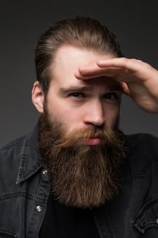 Młody modnisia mężczyzna patrzeje daleki odosobnionego na szarym tle z długą perfect brodą