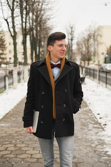 Młody modnisia mężczyzna z laptopem w ręce z miastowym spojrzeniem w mieście