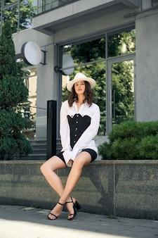 Młody modny biznes kobieta siedzi w pobliżu biurowca na ulicy miasta. stylowa modelka na sobie białą koszulę, czarny gorset, sandały, czapkę i spodenki rowerowe. koncepcja mody.