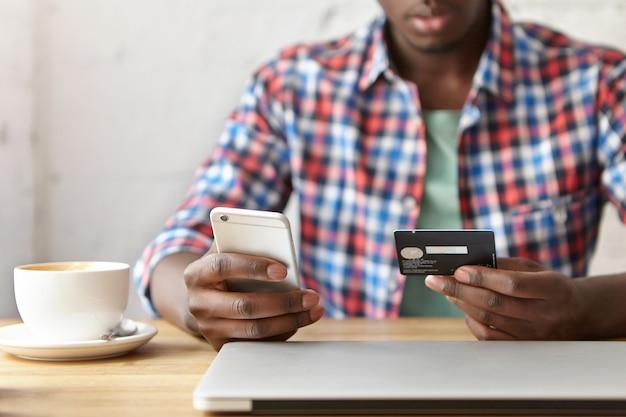 Młody modny facet siedzi w kawiarni ze smartfonem