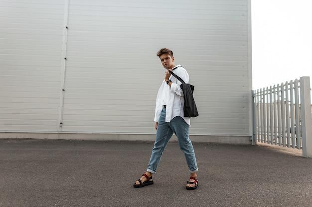 Młody modny młody człowiek spaceruje po mieście w letni dzień. przystojny miejski facet w modnych białych i dżinsowych ubraniach