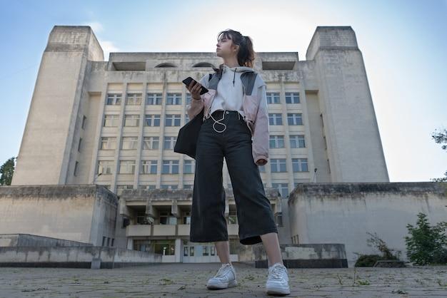 Młody modny nastoletni student stojący na ulicy