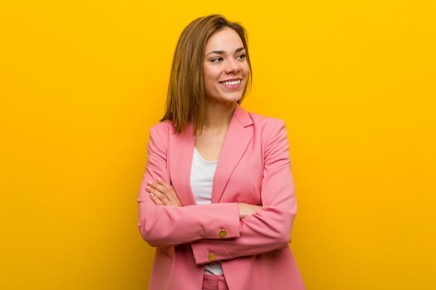 Młody mody biznesowej kobiety ono uśmiecha się ufny z krzyżować rękami.