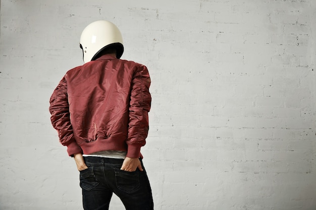Młody motocyklista w białym kasku i czerwonej nylonowej kurtce wystrzelony z tyłu z rękami w tylne kieszenie dżinsów w studiu o białych ścianach.