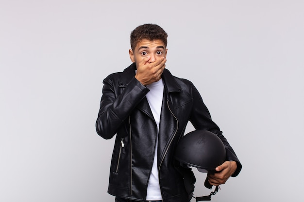 """Młody motocyklista zakrywający usta rękami z zszokowanym, zdziwionym wyrazem twarzy, dochowujący tajemnicy lub mówiąc """"ups"""""""