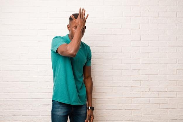 Młody murzyn, afroamerykanin, podnoszący dłoń do czoła, myślący ups, po popełnieniu głupiego błędu lub przypomnieniu sobie, czując się głupio na ścianie z cegły