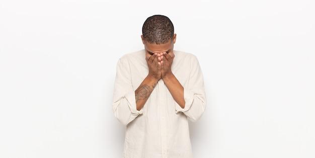 Młody murzyn czuje się smutny, sfrustrowany, zdenerwowany i przygnębiony, zakrywa twarz obiema rękami, płacze