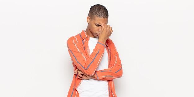 Młody murzyn czuje się zestresowany, nieszczęśliwy i sfrustrowany, dotyka czoła i cierpi na migrenę lub silny ból głowy