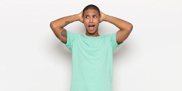 Młody murzyn czuje się zestresowany, zmartwiony, niespokojny lub przestraszony, z rękami na głowie, panikuje podczas pomyłki