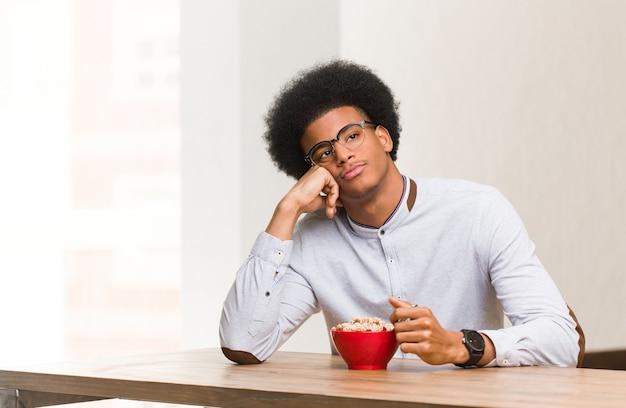 Młody murzyn jedząc śniadanie, myśli o czymś, patrząc w bok