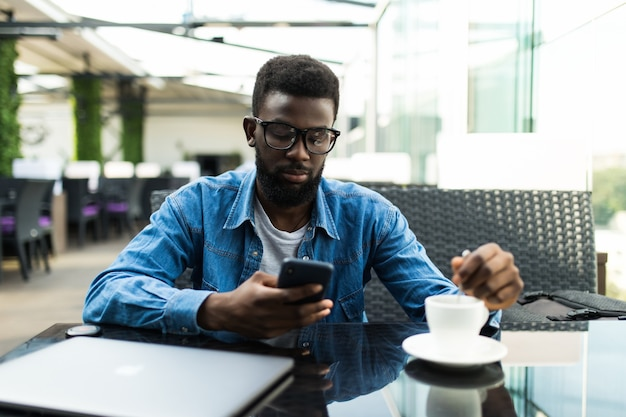 Młody murzyn na zewnątrz w kawiarni, patrząc na swojego smartfona