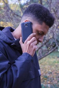 Młody murzyn opowiada na mądrze telefonie w lesie.