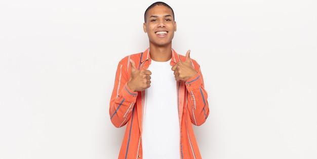 Młody murzyn, szeroko uśmiechnięty, szczęśliwy, pozytywny, pewny siebie i odnoszący sukcesy, z dwoma kciukami do góry