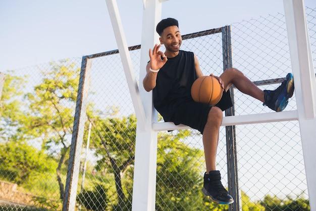 Młody murzyn uprawia sport, gra w koszykówkę, aktywny tryb życia, letni poranek, uśmiechnięty zadowolony z zabawy